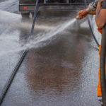 Nova Caine pressure cleaning the road