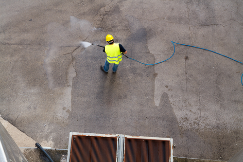 Man power washing cement ground. Photo has long hose. Man holding on to wand