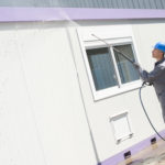 Man cleaning exterior of purple building